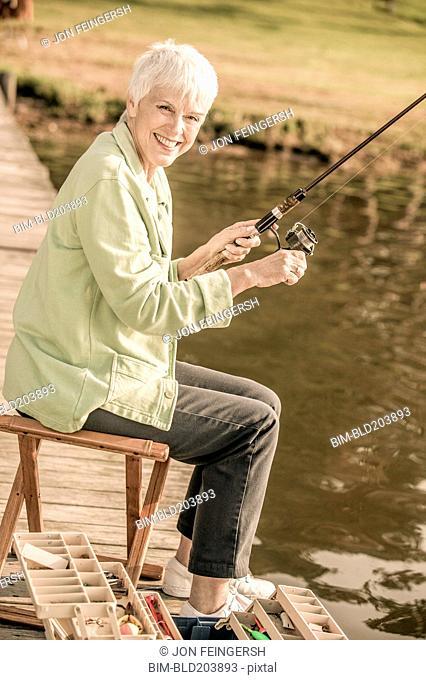 Older Caucasian woman fishing in rural lake