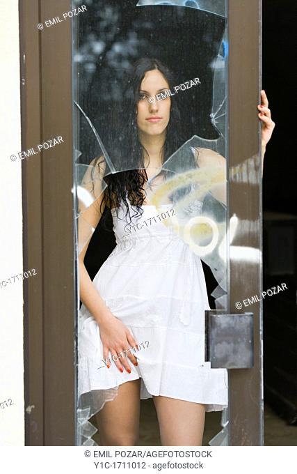 Young woman provocative behind a broken glass