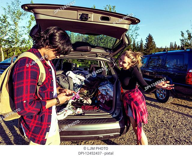 Young couple standing at the back of their packed vehicle with back door open and the young man in using his cell phone while the young woman waits impatiently;...