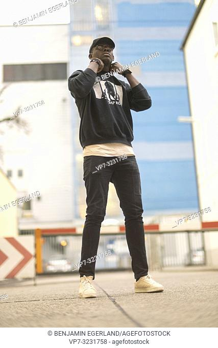 man wearing casual urban men's fashion street style clothes, at industrial area in Munich, Germany