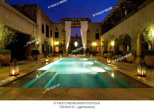 Morocco, Marrakesh, traditional restored riad Caravan Serai,  central courtyard view at dusk swimming pool