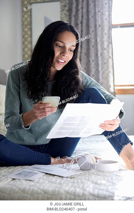 Hispanic woman sitting on bed with cell phone and bills