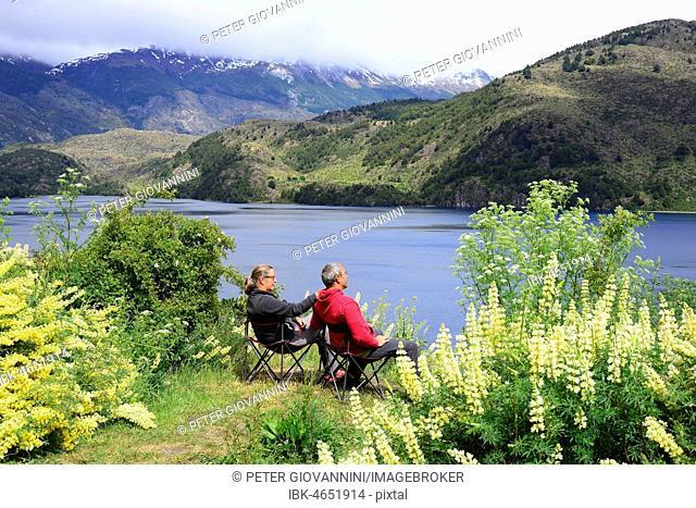 Couple on camping chairs at Lago Tranquilo, Valle Exploradores, near Puerto Rio Tranquilo, Región de Aysén, Chile
