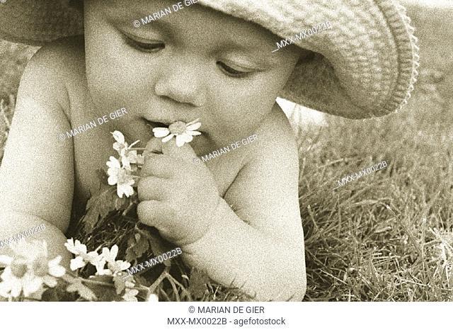 Portrait of a baby in a hat playing with flowers