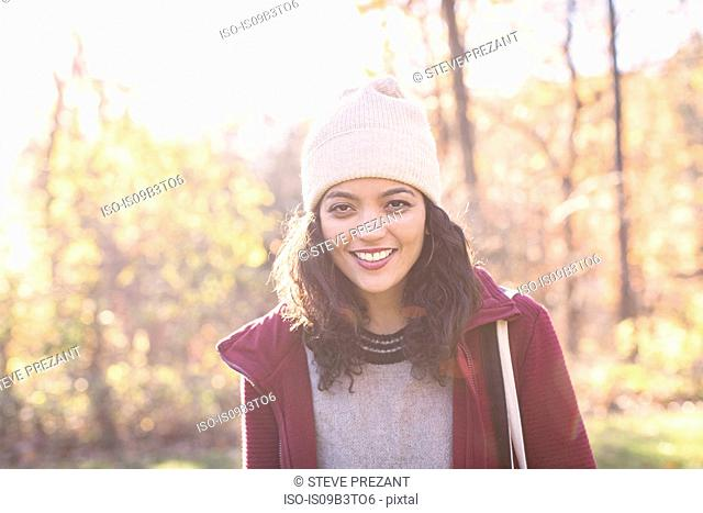 Portrait of young woman wearing knit hat in autumn