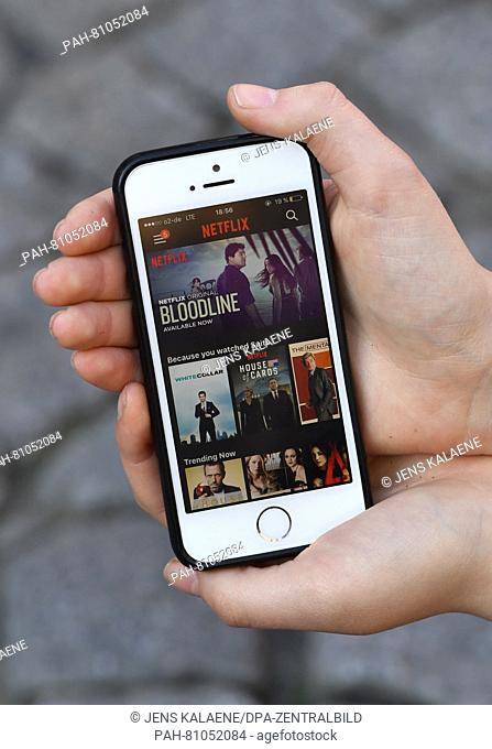 A young woman uses an app by streaming provider Netflix on her smartphone, photographed at the premiere of the Netflix series 'Orange is the new Black - 4th...