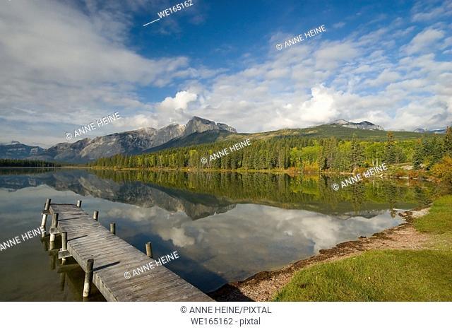 Catwalk at lake with blue sky and Rocky Mountains (Mount Yamnuska). Lake in front of Nakoda Lodge, Indian National Reserve (Nakoda, Stoney First Nations)