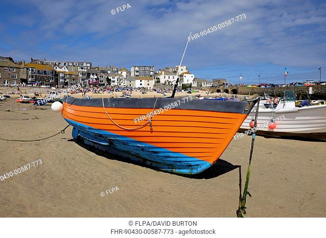 Brightly coloured fishing boat moored on beach, St. Ives, Cornwall, England, August