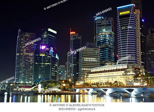 night skyline of singapore business district and marina bay  the building in the foreground is the fullerton hotel while the statue on bottom left is the...