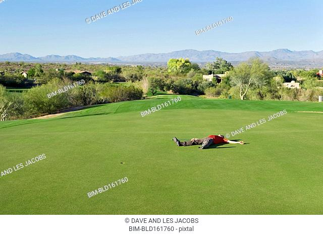 Exhausted Caucasian man laying on golf course
