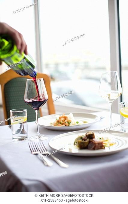 Pouring a glass of red wine to accompany a meal lunch dinner for two in a hotel restaurant
