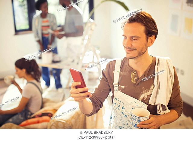 Man painting living room, drinking coffee and checking smart phone