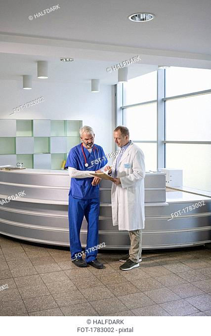 Male doctors discussing medical record in hospital