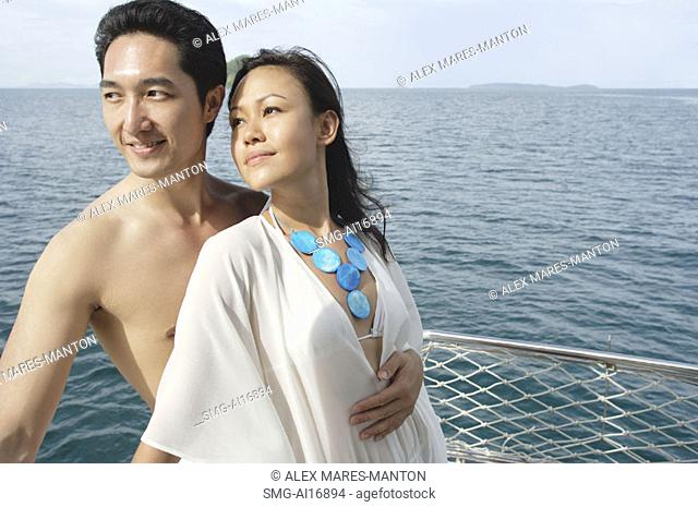 Couple standing on yacht