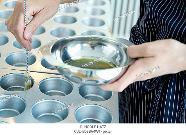Chef brushing oil onto baking tray, mid section, close-up