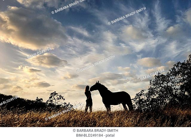Silhouette of Caucasian woman and horse standing in landscape
