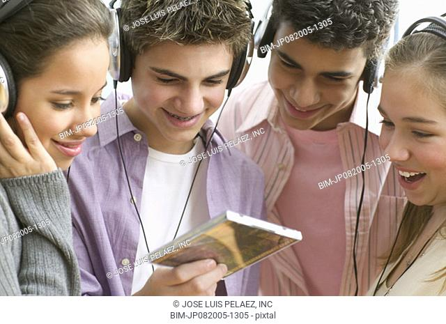 Four teenagers with headsets listening to music