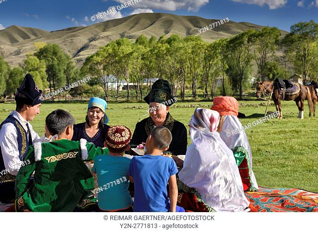 Laughing family in traditional garb at a picnic in pasture of Chilik river valley at Saty Kazakhstan