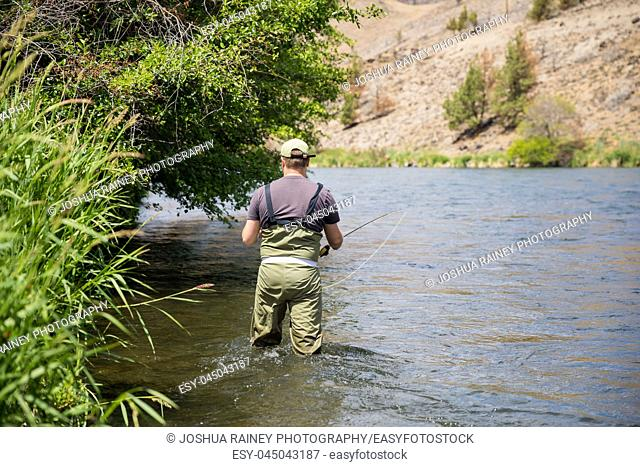 Fly fisherman casting to rising native redside rainbow trout on the Lower Deschutes River in Oregon. The Deschutes is listed as Wild and Scenic