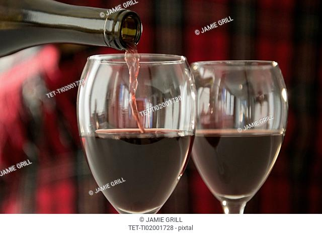 Studio Shot of pouring red wine into wine glasses