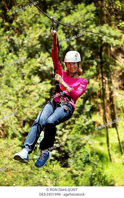 Woman zip-lining at Skyline Eco-Adventure; Kula, Maui, Hawaii, United States of America