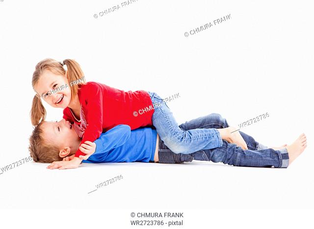 brother and sister having fun with each other - isolated on white