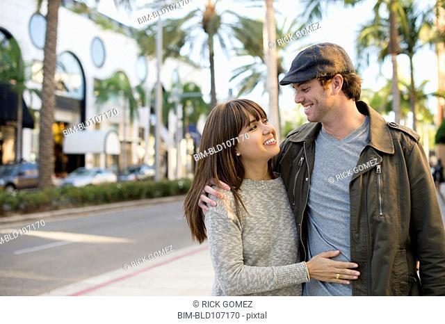 Smiling couple walking on city street