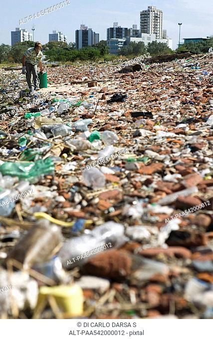 Male collecting trash in polluted landscape
