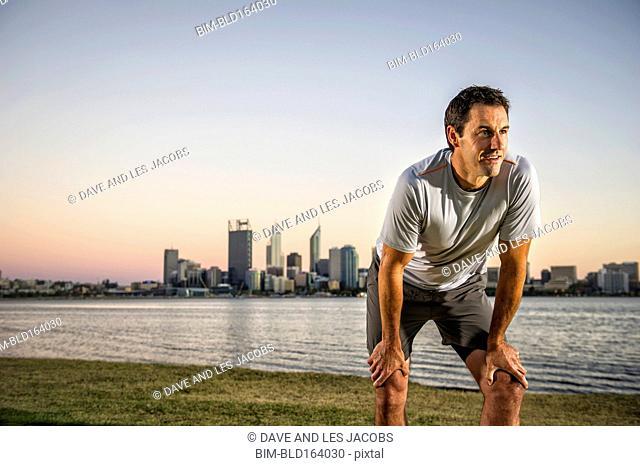 Caucasian runner resting near urban waterfront, Perth, Western Australia, Australia
