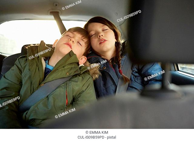 Boy and sister asleep in car backseat
