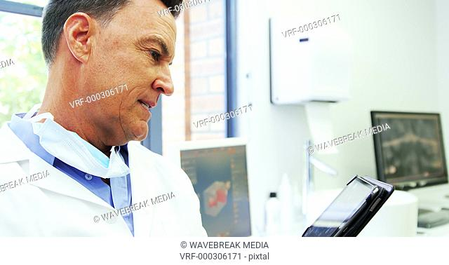 Portrait of smiling dentist using digital tablet