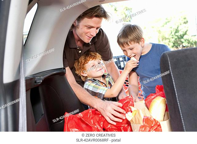 Boys eating groceries in trunk of car