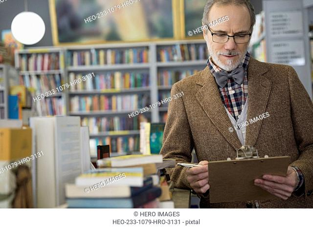 Bookstore owner with clipboard taking inventory
