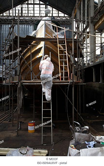 Worker climbing ladder to spraypaint boat in shipyard