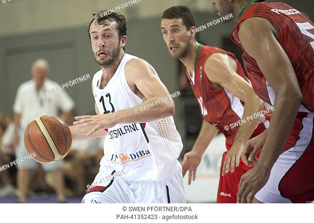 Germany's Bastian Doreth (L) plays against Portugal's Joao Balseiro () and Claudio Fonseca during the international basketball match Germany vs