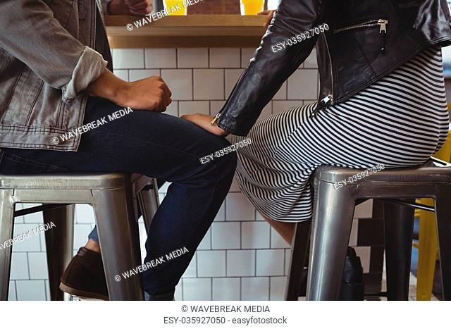 Low section of couple on stool in cafe