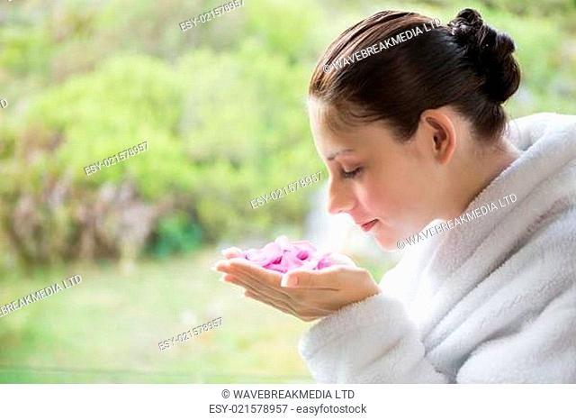 Side view of beautiful young woman smelling flowers