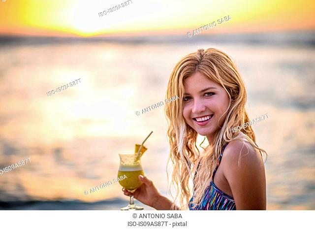 Portrait of young woman drinking cocktail on beach at sunset