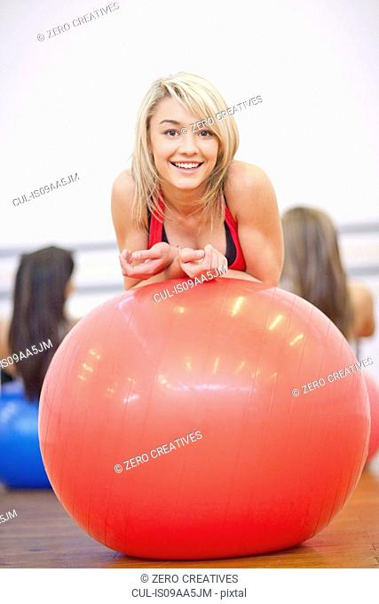 Young woman resting on exercise ball in aerobics class