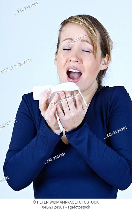 young woman sneezing (model-released)