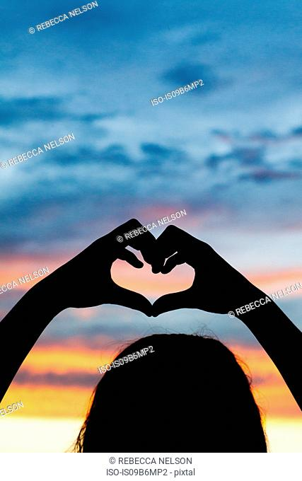 Silhouette of girl making heart with her hands against dramatic sky