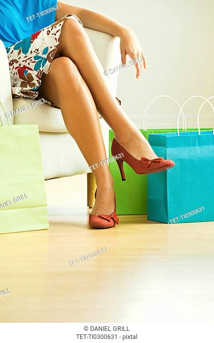 Woman sitting beside shopping bags