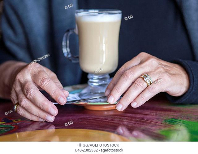 Close up of Womans hands drinking capuchino