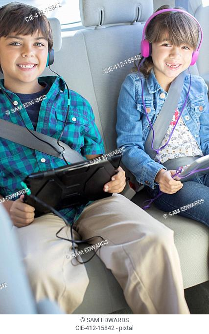 Portrait of happy brother and sister with headphones using digital tablets in back seat of car