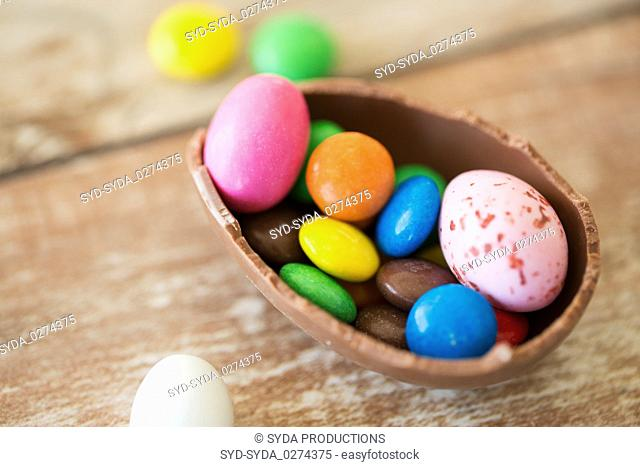 chocolate easter egg and candy drops on table