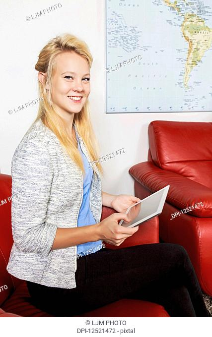 A beautiful young millennial business woman with long blond hair using her tablet in the lobby of a workplace while waiting for a job interview; Sherwood Park