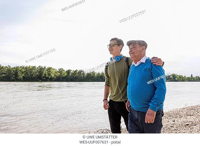 Grandfather and grandson standing at riverside looking together at distance