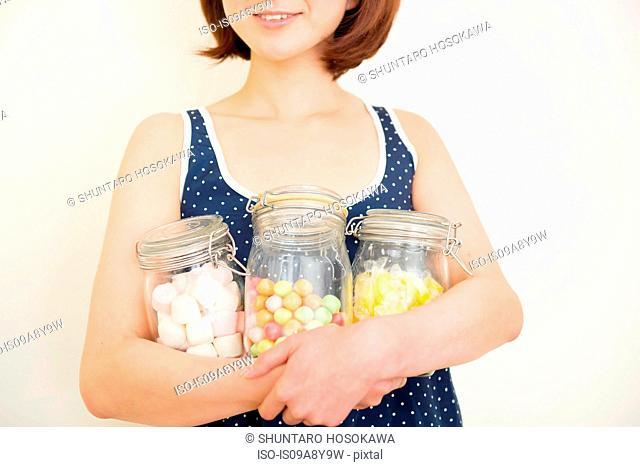 Woman hugging three jars of marshmallows, bubble gum and sherbet lemons