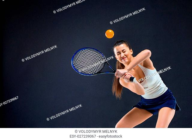 Portrait of beautiful girl tennis player with a racket on dark studio background