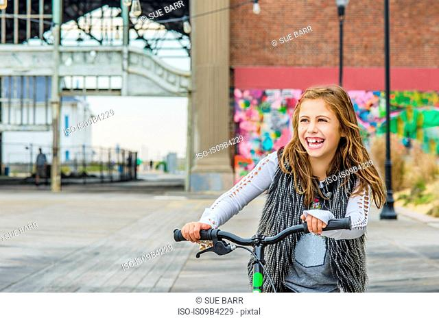 Girl with push scooter in urban setting